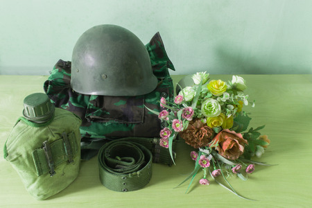 disordered: Still life  photography on vintage army helmet and flower Stock Photo