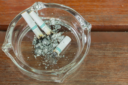 then: Smoking and then placed in an ashtray.on wood background