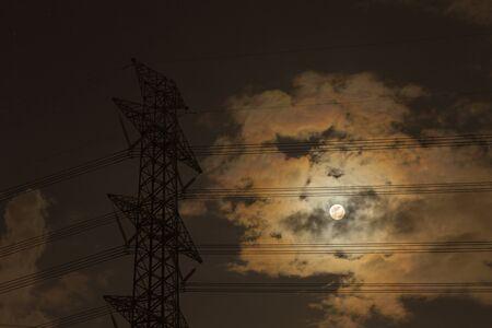 megawatts: high voltage tower at night.