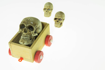 ship with gift: Skull on a toy carriage on white background. Stock Photo