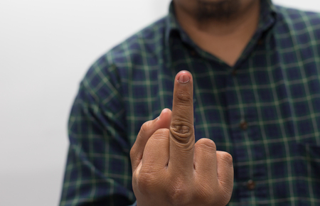 carelessness: Man wearing glasses showing the middle finger