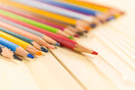 polychromatic: One  red pencil standing out from the other colors. on wood background