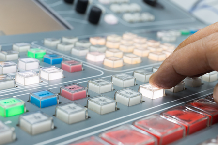 cinematographer: Hands of a cinematographer who worked on the vision mixer, switch the TV panel to the gallery. Stock Photo
