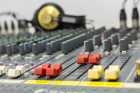 Photograph of a fader mixer red color, taken close up with a shallow depth of field. Background equipment and headphone. Stock Photo
