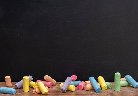 Group of colorful chalks on wood table with blackboard or chalkboard as background, concept for education, back to school.