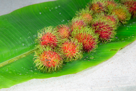 Fresh Rambutan on banana leaf background Stock Photo