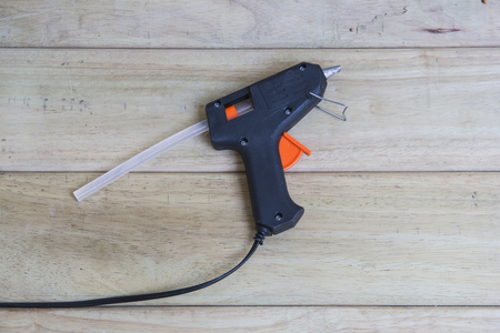 joining forces: Electric hot glue gun on a wood background.