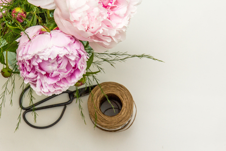 Peonies with tools on white background.