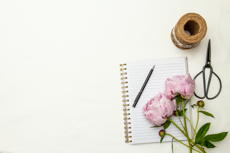 Peonies with notebook and tools on white