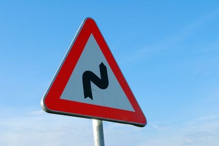 warning bendy road ahead sign with blue sky Stock Photo - 5098447