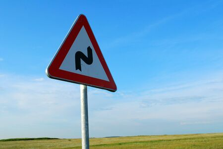 warning bendy road ahead sign with blue sky  Stock Photo - 5098448