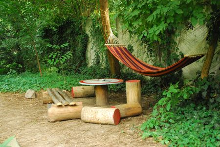 a net hammock hanging between trees in the backyard Foto de archivo