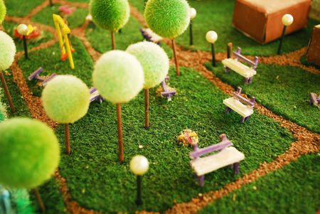 miniature people: detail of a garden maquette with trees and playground Stock Photo