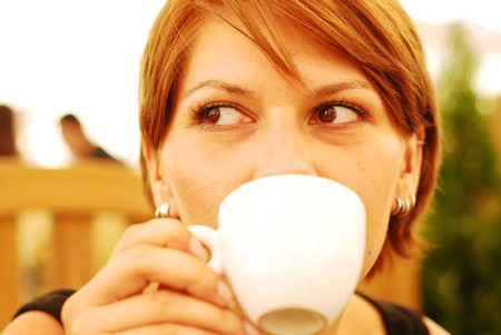 A beautiful young woman holding a cup of hot coffee Stock Photo - 7561430