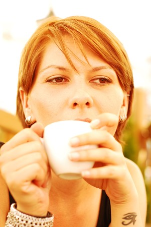 A beautiful young woman holding a cup of hot coffee Stock Photo - 7561428