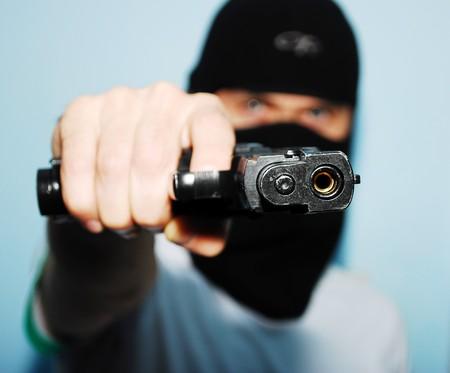 若い男が彼の銃の焦点と銃を保持しています。