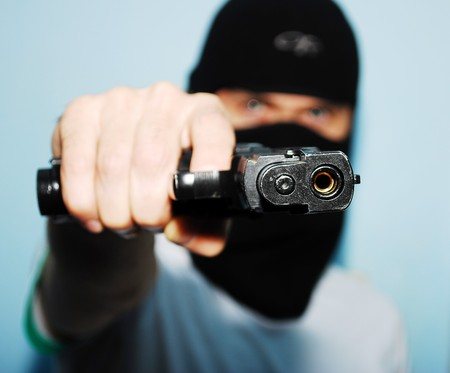 Young man holding up a gun with the focus on his gun Stock Photo - 8029937