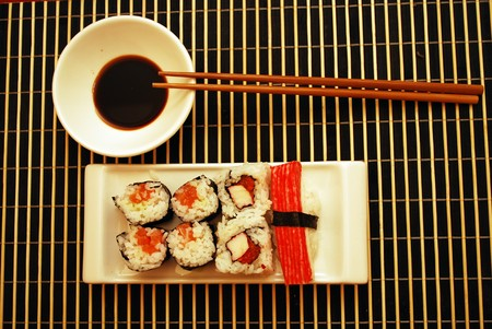 Seafood traditional sushi and rolls on the white dish. Banco de Imagens