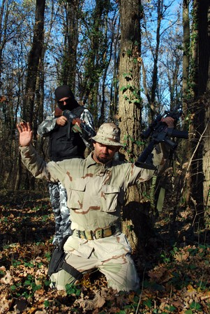 under arrest: US soldiercriminal taking armed US soldier under arrest with forest behind Stock Photo