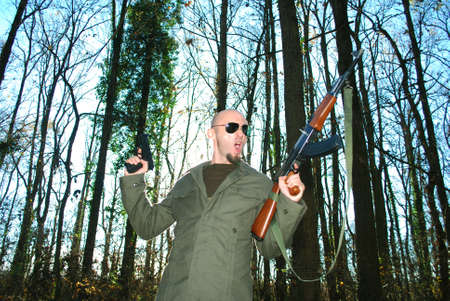young man impersonating revolutionary in the forest with guns photo