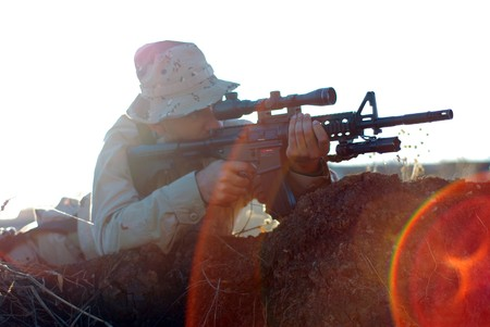 Soldier in camouflage aiming with his rifle outdoor with lens flare effect photo