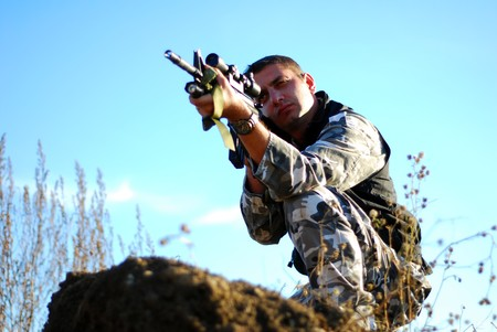 Soldier in camouflage aiming with his rifle outdoor photo