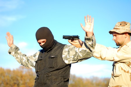 under arrest: US soldier taking armed criminal under arrest with blue sky behind