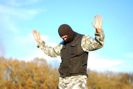 The surrendered criminal in a black mask  with blue sky behind photo