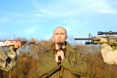 guerilla: one guerilla soldier with many weapons pointed to his head
