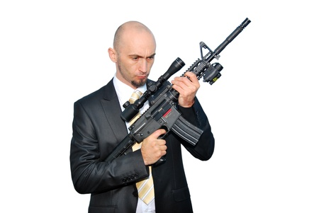 Businessman bodyguard isolated on a white background with a big gun photo