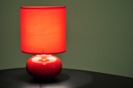 image of a red table lamp sitting on a brown desk photo