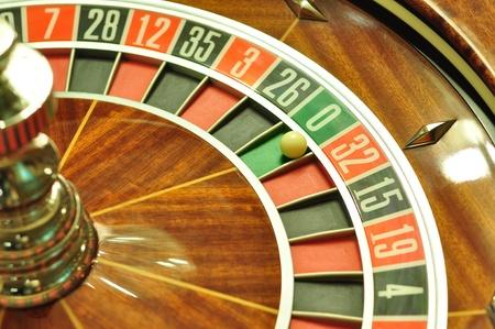 roulett: Bild mit einem Casino-Roulette-Rad mit dem Ball auf Nummer 0