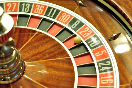 image with a casino roulette wheel with the ball on number 23 photo