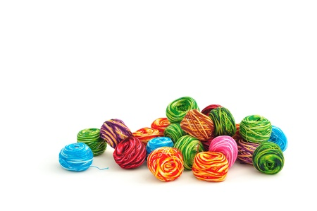 close up of many colorful balls of thread on white background
