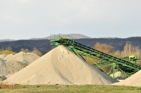 Conveyor on site at gravel pit with sand pile photo