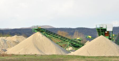 gravel pit: Conveyor on site at gravel pit with sand pile