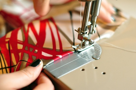 Color Image with Hands of Seamstress Using Sewing Machine photo