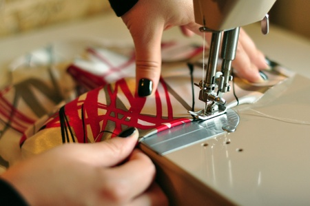 textile industry: Color Image with Hands of Seamstress Using Sewing Machine