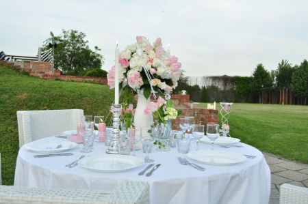 wedding table: image of a romantic outdoor table prepared for dinner with flowers Stock Photo