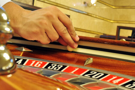 casino dealer fingers holding the ball and prepare for launching photo