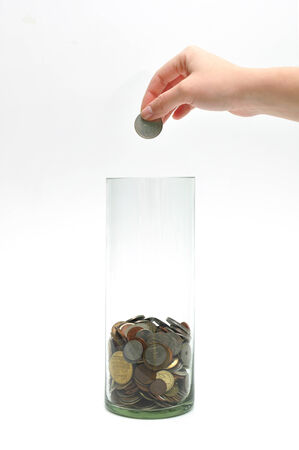 dime: woman hand dropping coin into glass jar