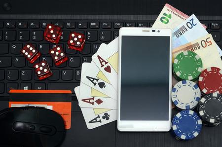 fichas de casino: computadora en l�nea del casino concepto de juegos y tel�fonos inteligentes
