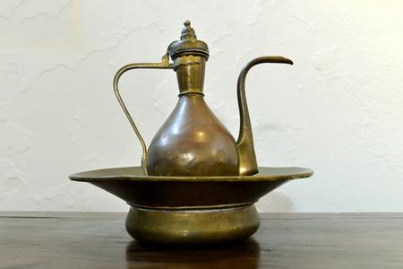 wash basin: ancient greek wash basin and jug over white wall