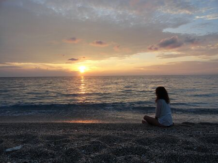 mujeres pensando: young woman meditating on a greek beach at sunset Foto de archivo