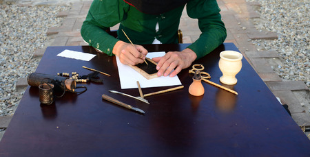 Medieval scribe writing a text hands close detail