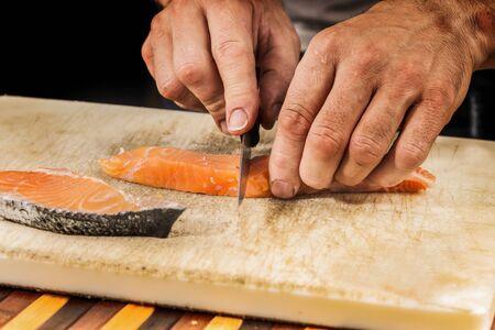 fishmonger: fishmonger prepares a salmon fillet