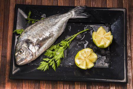 sea bream: sea bream vegetable and lemon on a black plate Stock Photo