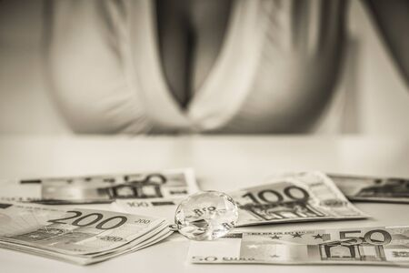 pechos: chica con pechos grandes y un escritorio con los billetes de banco Foto de archivo