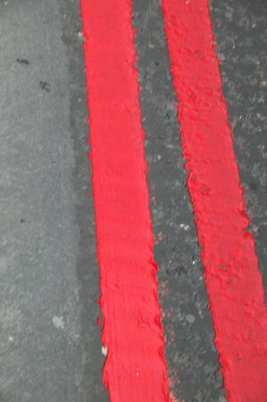 traffic warden: Red lines are painted on the UK streets as a warning that you may not park  your vehicle at any time.