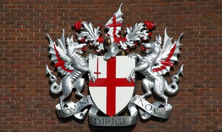 17th: In 1380 the red cross of St.George and the sword of St.Paul were adopted as the city of Londons arms. The dragon supports were added later in the 17th century. The Latin motto means Lord guide us